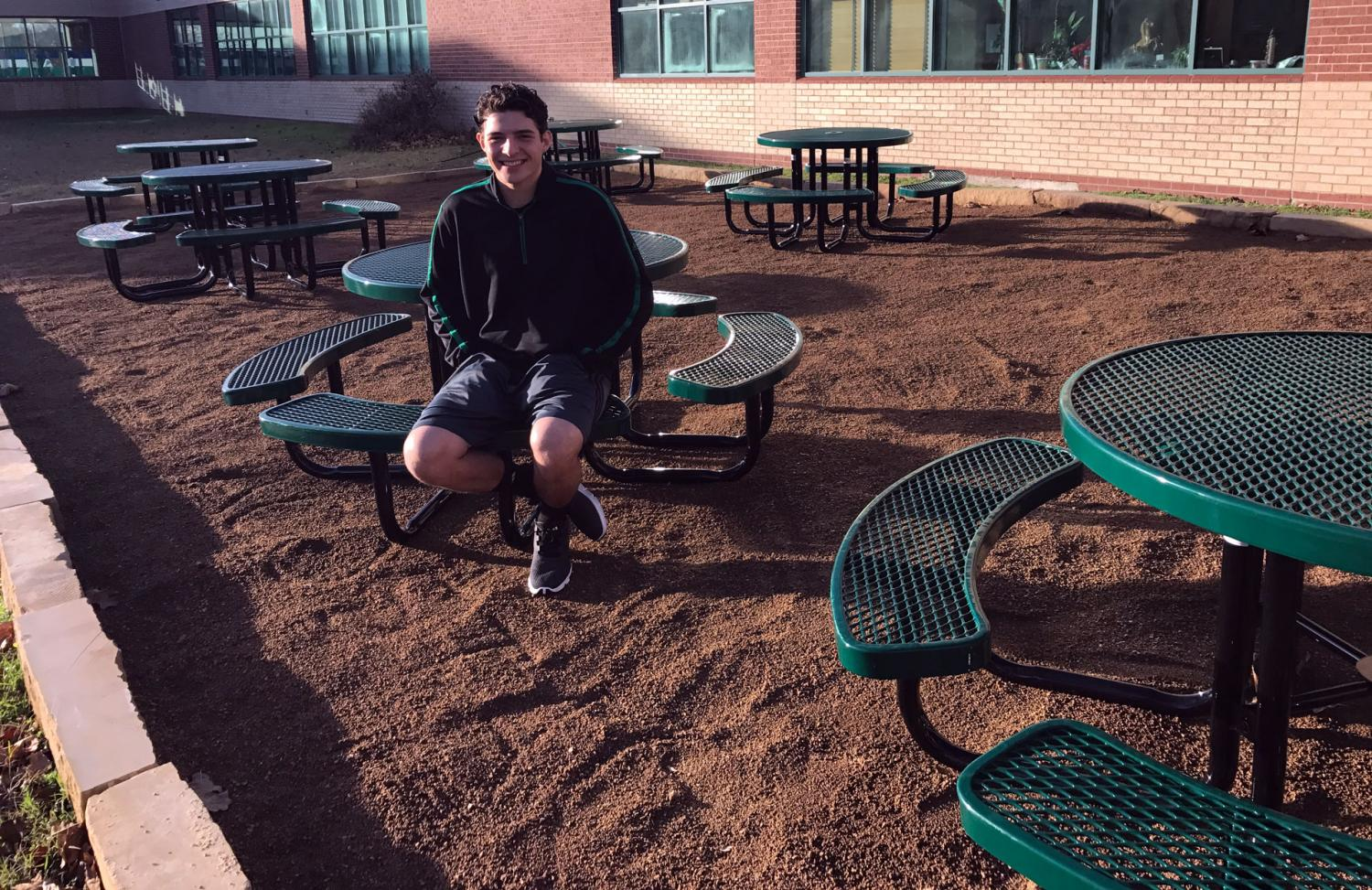 After completing the outdoor classroom in the center courtyard, senior Luke Guajardo tries out the benches. As his Eagle Scout project, Guajardo partnered with Environmental Science teacher Tina Vick, who had the the vision to create an alternate learning environment for all courses to use.
