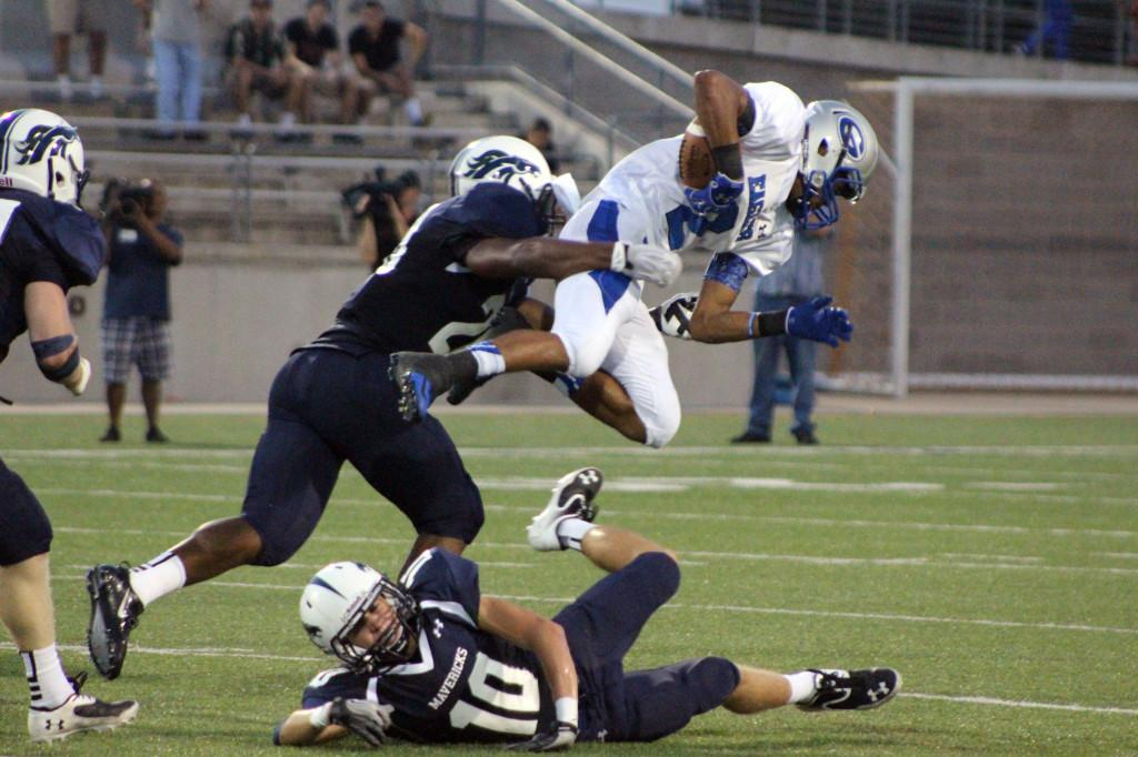In the home opener, junior Deandre Conner tackles a hurdling Georgetown Eagle from behind.