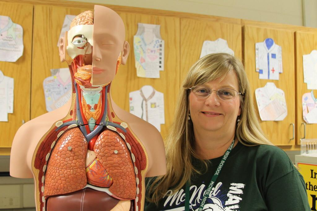 Hart-Sobkowiak strikes a pose next to an anatomical diagram in her classroom.