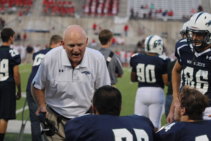 Coach Mike Newton with players during a football game.