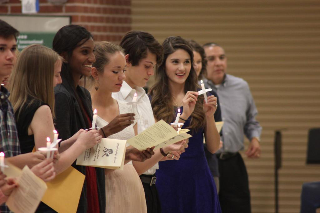 The new members of National Honor Society hold candles and recite the NHS pledge at the Induction Ceremony