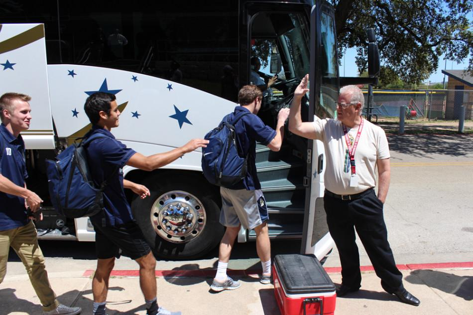 Players in line to high-five Mr. Vaden before boarding the bus.