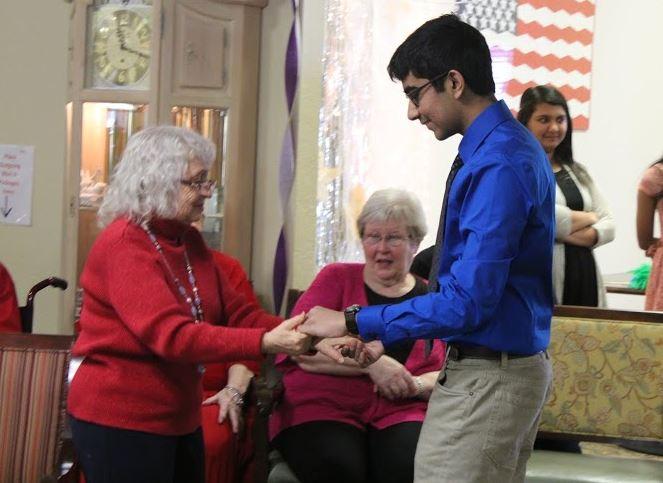 Saheel Chodavadia dancing with a senior citizen resident.
