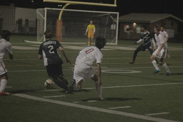 Shawn Murray dribbles through two defenders before crossing the ball in for a shot on goal
