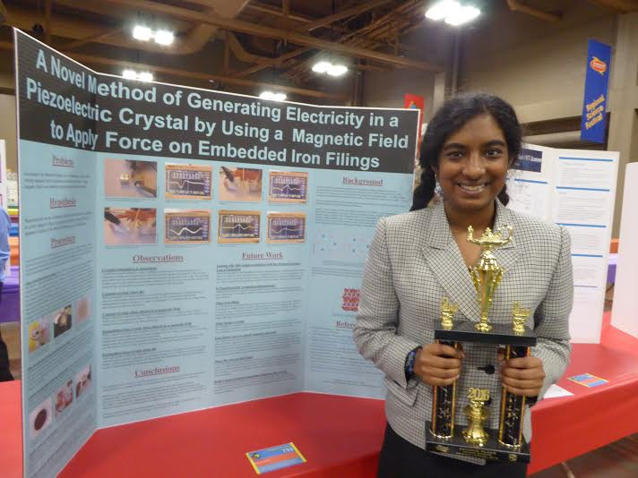 Kolagotla (10) holds her trophy in front of her science fair project.