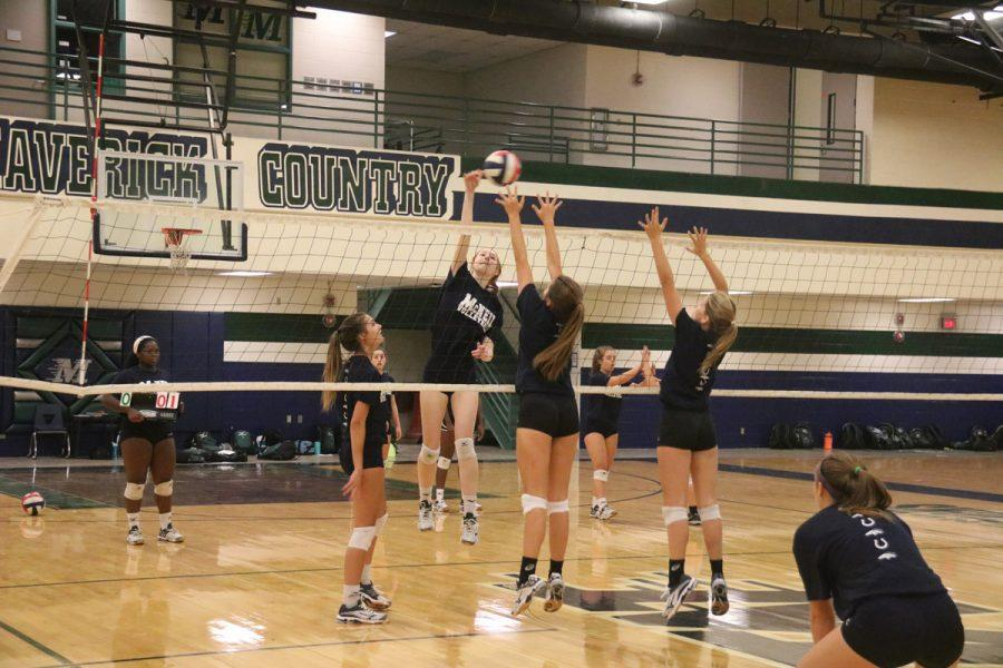 The Varsity volleyball team practices hitting and blocking.