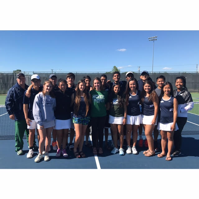 The+varsity+tennis+team+pose+in+the+court+after+several+individuals+succeeded+in+their+match.