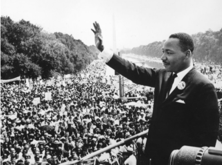 "Martin Luther King Jr. waving to the crowd as he delivers his ""I Have a Dream"" speech in Washington, D.C."