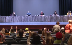 At the request of Board President Weir, audience members use jazz hands to silently applaud a speaker.